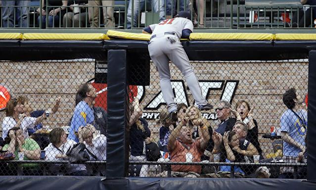 Minnesota Twins right fielder Oswaldo Arcia hangs on the wall as he can't get to a two-run home run hit by Milwaukee Brewers' Mark Reynolds during the fifth inning of a baseball game Monday, June 2, 2014, in Milwaukee. (AP Photo/Morry Gash)