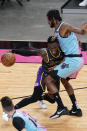 Los Angeles Lakers guard Dennis Schroder (17) tries to dribble around Miami Heat forward Trevor Ariza (8), during the first half of an NBA basketball game, Thursday, April 8, 2021, in Miami. (AP Photo/Marta Lavandier)