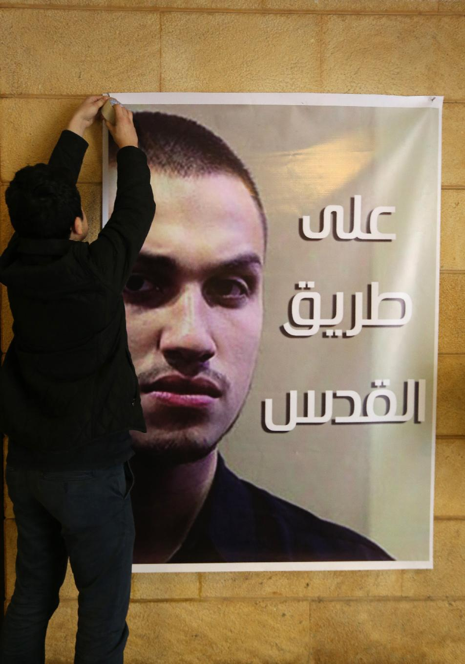 "A portrait of killed Jihad Mughniyeh with a slogan reading in Arabic, ""on the road to Jerusalem"" hangs at the ""Martyr's cemetery"" in a southern Beirut suburb on January 19, 2015 (AFP Photo/Joseph Eid)"