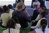 Prince Harry, the Duke of Sussex, adjusts his mask as he sits among students during a book reading by his wife Meghan, the Duchess of Sussex, during their visit to P.S. 123, the Mahalia Jackson School, in New York's Harlem neighborhood, Friday, Sept. 24, 2021. (AP Photo/Richard Drew)