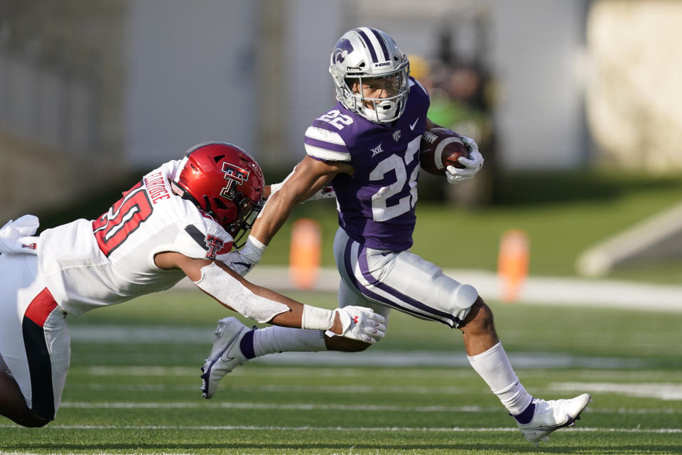 Kansas State running back Deuce Vaughn (22) gets past Texas Tech linebacker Kosi Eldridge (20) as he runs for a first down during the second half of an NCAA college football game Saturday, Oct. 3, 2020, in Manhattan, Kan. (AP Photo/Charlie Riedel)