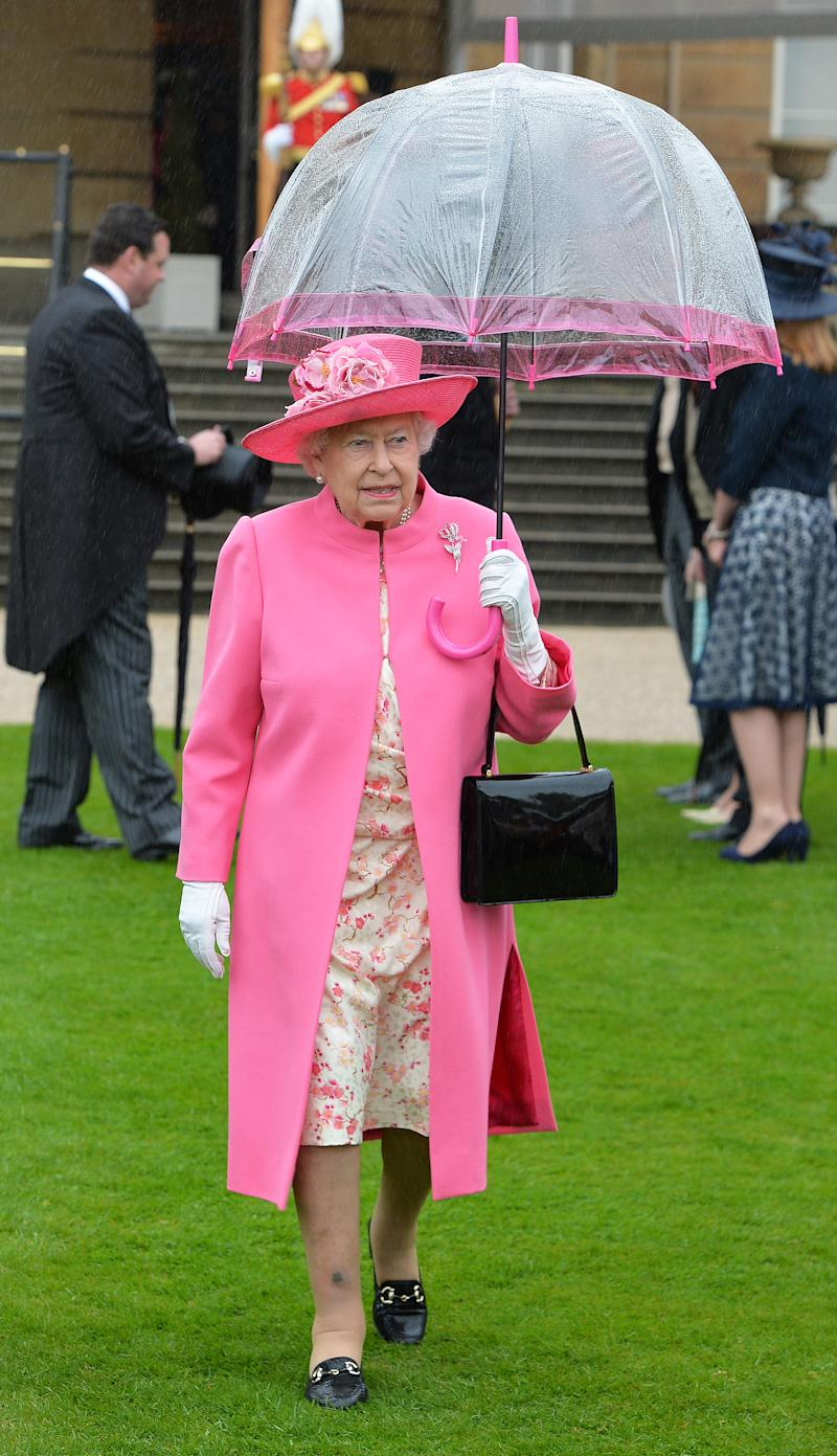 Britain's Queen Elizabeth II walks under an umbrella in the garden of Buckingham Palace in London as up to 8,000 guests attend the first royal garden party of the year on May 10, 2016. / AFP / POOL / John Stillwell (Photo credit should read JOHN STILLWELL/AFP/Getty Images)