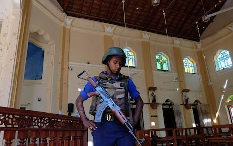 A police officer stands guard in Katuwapitiya St. Sebastian church in Negombo  - Credit:  REX