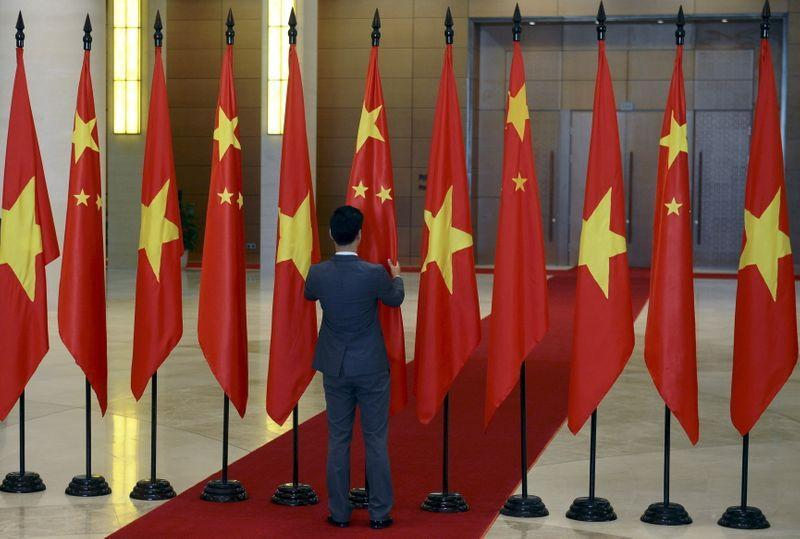 A Vietnamese protocol officer arranges Chinese and Vietnamese flags before the arrival of Chinese President Xi Jinping at the Parliament House in Hanoi