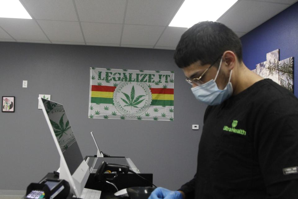 Store manager Estevan Mendoza, 21, operates a cash register at an Ultra Health medical cannabis dispensary onTuesday, June 29, 2021, in Santa Fe, New Mexico. Cannabis was legalized for recreational users in New Mexico this year. Residents with medical cards no longer have to pay tax on purchases and can now grow up to six plants. (AP Photo/Cedar Attanasio)