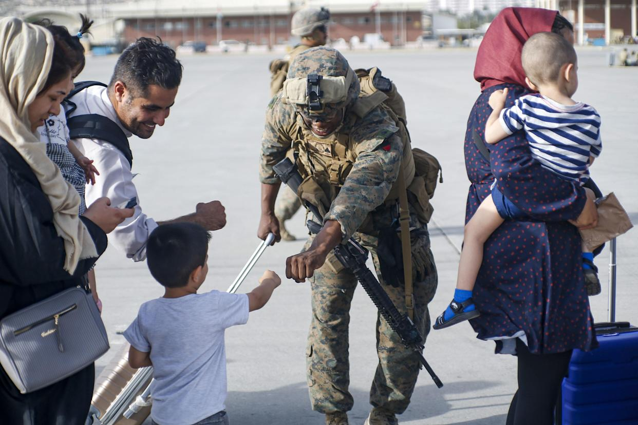 A U.S. Marine assigned to 24th Marine Expeditionary Unit fist bumps a child evacuee during a military drawdown at Hamid Karzai International Airport, Afghanistan, on August 18, 2021.  (Lance Cpl Nicholas Guevara/USMC/UPI/Shutterstock)