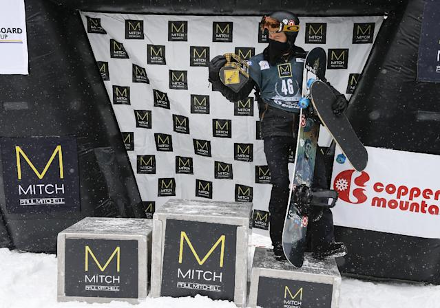 Shaun White glances at one of his prizes as he stands in the third place spot on the podium after competing in the World Cup U.S. Grand Prix slopestyle snowboarding finals, Sunday, Dec. 22, 2013, in Frisco, Colo. (AP Photo/Julie Jacobson)