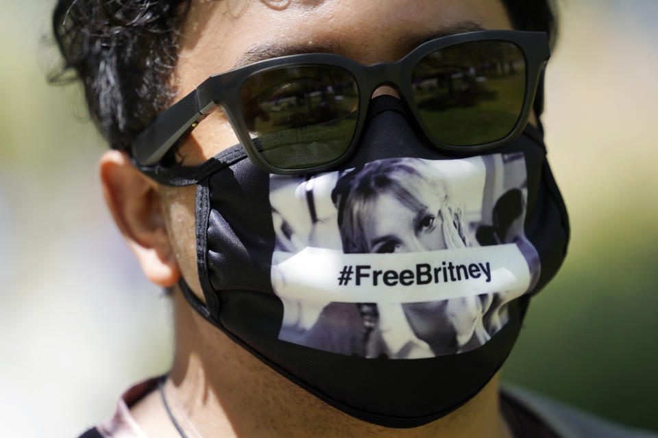 Britney Spears supporter Carlos Morales of Los Angeles wears a Free Britney mask outside a court hearing concerning the pop singer's conservatorship at the Stanley Mosk Courthouse, Wednesday, June 23, 2021, in Los Angeles. (AP Photo/Chris Pizzello)