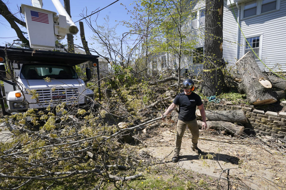 Austin Even, of Independence, Iowa, clears branches from in front of a home, Friday, April 30, 2021, in Cedar Rapids. A rare storm called a derecho plowed through the city of 130,000 last August with 140 mph winds and left behind a jumble of branches, downed powerlines and twisted signs. Now, city officials, businesses and nonprofit groups have teamed up with ambitious plans to somehow transform what is now a city of stumps back into the tree-covered Midwestern oasis along the Cedar River. (AP Photo/Charlie Neibergall)
