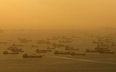 FILE PHOTO: Shipping vessels and oil tankers line up on the eastern coast of Singapore