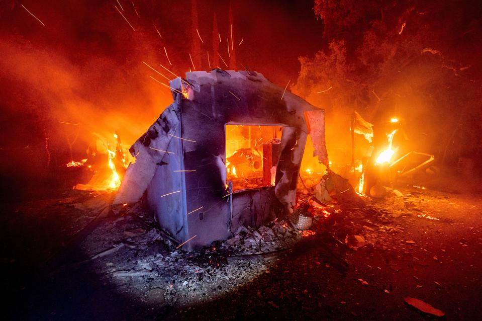 Flames from the LNU Lightning Complex fires consume a home in unincorporated Napa County, Calif., on Aug. 19, 2020. Fire crews across the region scrambled to contain dozens of wildfires sparked by lightning strikes.