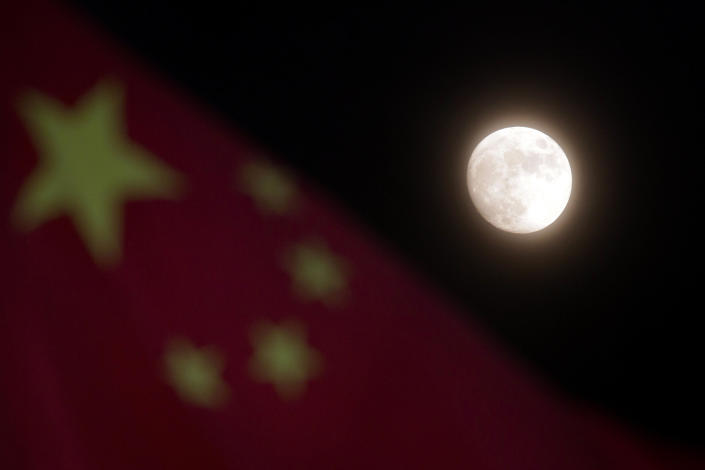 The moon is seen near a Chinese national flag in Beijing Sunday, Dec. 15, 2013. China's first moon rover touched the lunar surface and left deep traces on its loose soil, state media reported Sunday, several hours after the country successfully carried out the world's first soft landing of a space probe on the moon in nearly four decades. (AP Photo/Ng Han Guan)