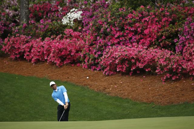 Rory McIlroy of Northern Ireland chips to the 13th green after hitting into the azaleas during third round play of the 2018 Masters golf tournament at the Augusta National Golf Club in Augusta, Georgia, U.S. April 7, 2018. REUTERS/Mike Segar