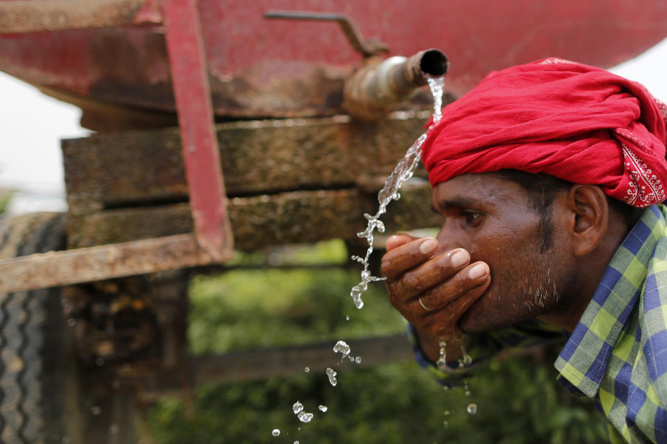 Indian laborer drinks water from a mobile tanker after planting saplings as part of an annual tree plantation campaign on the outskirts of Prayagraj, in northern Uttar Pradesh state, India, Sunday, July 4, 2021. (AP Photo/Rajesh Kumar Singh)