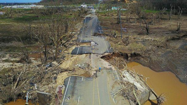 PHOTO: A man rides his bicycle through a damaged road in Toa Alta, west of San Juan, Puerto Rico, Sept. 24, 2017, following the passage of Hurricane Maria. (Ricardo Arduengo/AFP/Getty Images, FILE)