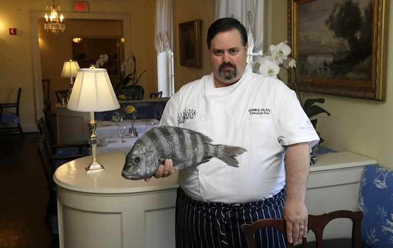 """In this photo taken Thursday, June 13, 2013, James Clark, Executive Chef at Carolina Crossroads Restaurant holds a fresh sheepshead fish ready to be prepared for dining in Chapel Hill, N.C. Chefs such as Clark go beyond the usual recommendation to eat small, lower-food-chain fish like sardines, and instead delve full force into little-known local catches that many anglers regard as nuisance or """"trash"""" fish. (AP Photo/Gerry Broome)"""