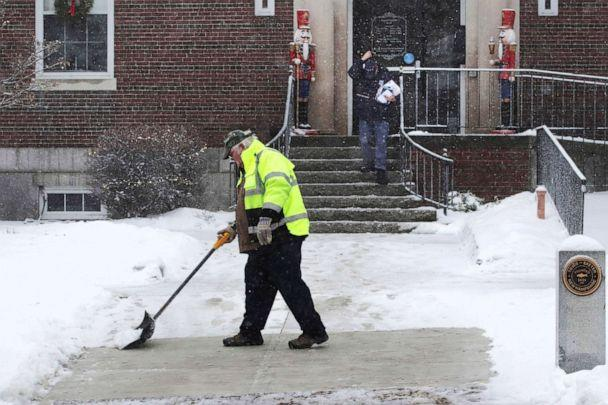 PHOTO: A worker shovels a coating of crusty snow from the walkway outside town hall during a snow storm in Exeter, N.H., Dec. 30, 2019. The southern New Hampshire area received a coating of snow and ice during the winter storm. (Charles Krupa/AP)