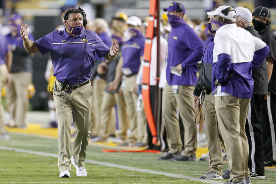 LSU head coach Ed Orgeron, left, reacts after a play during the first half of an NCAA college football game against South Carolina in Baton Rouge, La., Saturday, Oct. 24, 2020. (AP Photo/Brett Duke)