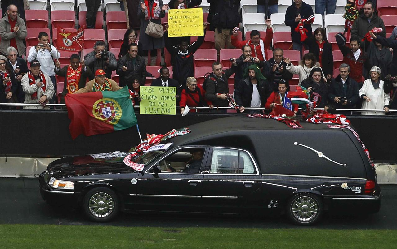 "The hearse carrying the coffin of Eusebio crosses the Luz stadium in Lisbon January 6, 2014. Portuguese great Eusebio, top scorer at the 1966 World Cup, died on Sunday from a heart attack at the age of 71 with the small Iberian nation mourning him as an ""eternal symbol"" of their football pride. The Portuguese government declared three days of national mourning and many fans paid homage by visiting an iconic statue of him erected next to Benfica's Luz stadium, leaving flowers, scarves and other tributes. On Monday, he was honored at Luz stadium before his burial. REUTERS/Hugo Correia (PORTUGAL - Tags: SPORT SOCCER OBITUARY)"