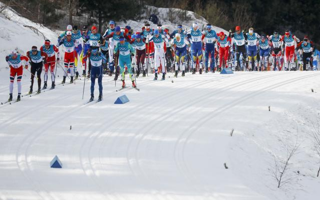Cross-Country Skiing - Pyeongchang 2018 Winter Olympics - Men's 50km Mass Start Classic - Alpensia Cross-Country Skiing Centre - Pyeongchang, South Korea - February 24, 2018 - Niklas Dyrhaug of Norway and Jean Marc Gaillard of France lead the pack in the first lap. REUTERS/Kai Pfaffenbach