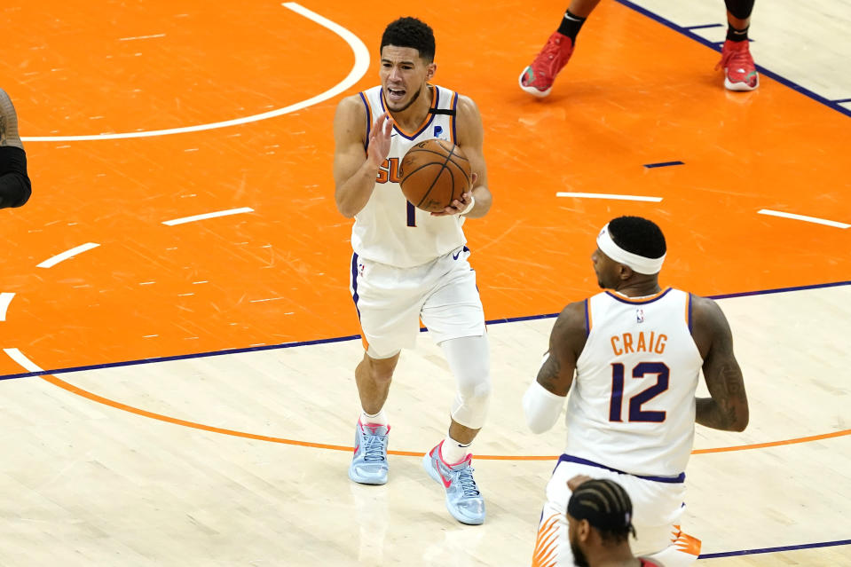Phoenix Suns guard Devin Booker (1) reacts after turning the ball over against the Portland Trail Blazers during the second half of an NBA basketball game, Thursday, May 13, 2021, in Phoenix. (AP Photo/Matt York)