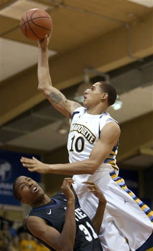 Butler forward Kameron Woods (31) defends as Marquette forward Juan Anderson (10) puts up a shot in the first half of an NCAA college basketball game Monday, Nov. 19, 2012, in Lahaina, Hawaii. Woods was called for a foul on the play. (AP Photo/Eugene Tanner)