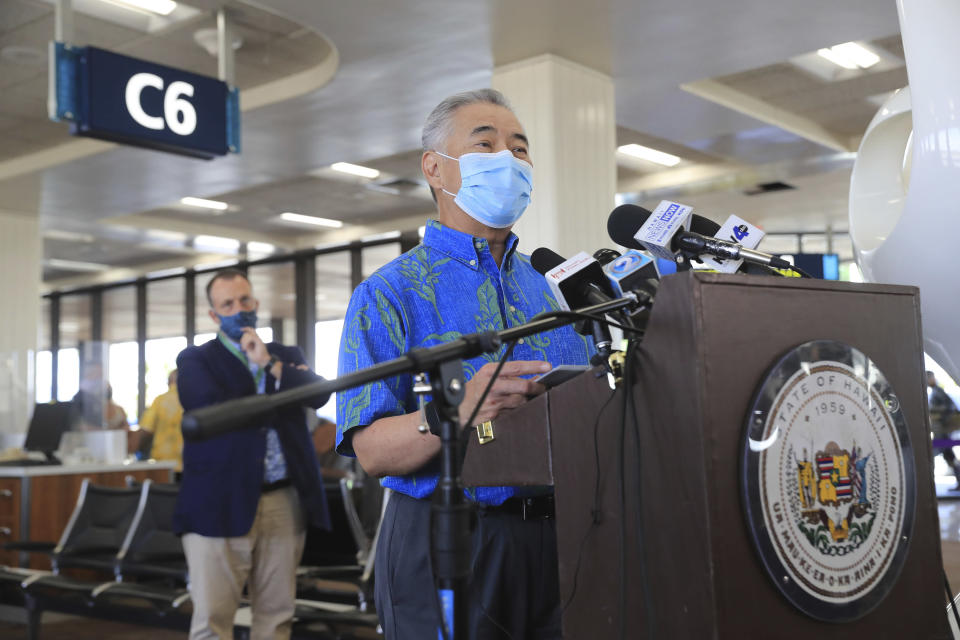 With Hawaii Lt. Gov Josh Green, left, in the background, Hawaii Gov. David Ige speaks at a press conference at the Daniel K. Inouye International Airport Thursday, Oct. 15, 2020, in Honolulu. A new pre-travel testing program will allow visitors who test negative for COVID-19 to come to Hawaii and avoid two weeks of mandatory quarantine goes into effect Thursday. The pandemic has caused a devastating downturn on Hawaii's tourism-based economy. Coronavirus weary residents and struggling business owners in Hawaii will be watching closely as tourists begin to return to the islands. (AP Photo/Marco Garcia)