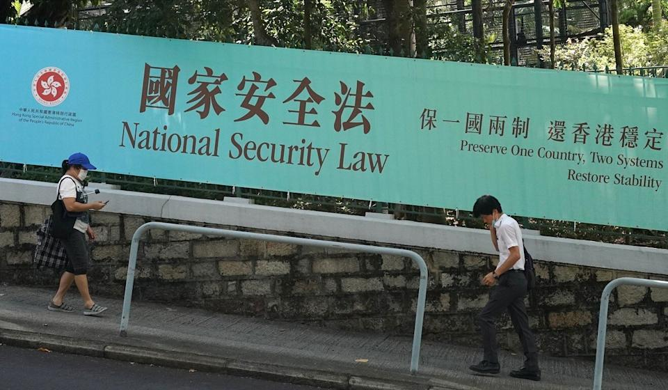 People walk past a banner advertising the National Security Law on Albany Road in Central. Photo: Felix Wong