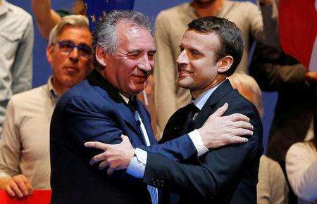 Emmanuel Macron (R), head of the political movement En Marche! (Onwards!) and candidate for the 2017 presidential election, and Francois Bayrou, French centrist politician and the leader of the Democratic Movement (MoDem), embrace as they attend a campaign rally in Pau, France, April 12, 2017. REUTERS/Regis Duvignau