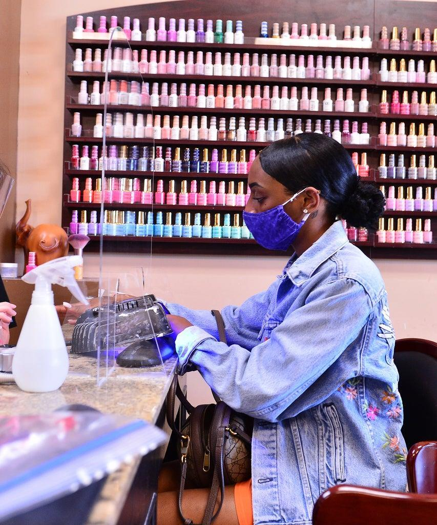 MIRAMAR, FL – MAY 20: Nail technician Habe is protected by a plexiglass barrier while giving a customer a manicure at Nails and Spa salon on May 20, 2020 in Miramar, Florida. The nail spa re-opened approximately two months after shutting its doors due to the coronavirus pandemic, as Broward County starts the first phase of the state's re-opening plan, which includes openings with certain restrictions of non-essential retail stores, barbershops, hair salons, and restaurants. (Photo by Johnny Louis/Getty Images)