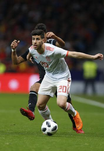 FILE - In this Tuesday, March 27, 2018 filer, Spain's Marco Asensio breaks away from Fabricio Bustos, rear, during the international friendly soccer match between Spain and Argentina at the Wanda Metropolitano stadium in Madrid, Spain. At the World Cup four years ago, Colombia forward James Rodriguez became one of the stars of the tournament and shot to international fame with his trickery on the ball and eye for a spectacular goal. Here's a look at young players hoping to make a similar impact at this year's World Cup in Russia. Among them is France left back Benjamin Mendy, Spain midfielder Marco Asensio, Belgium winger Leroy Sane, and Brazil striker Gabriel Jesus. (AP Photo/Francisco Seco, File)