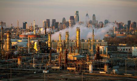 The Philadelphia Energy Solutions oil refinery is seen at sunset in front of the Philadelphia skyline
