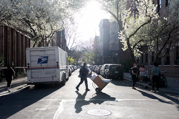 A USPS mail worker casts a shadow while wheeling boxes near Japanese Cherry Blossom trees  in the West village amid the coronavirus pandemic on April 07, 2021 in New York City. (Alexi Rosenfeld/Getty Images)