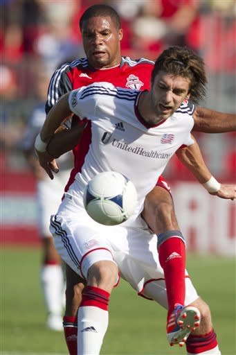 New England Revolution's Benny Feilhaber, front, holds off a challenge from Toronto FC's Ryan Johnson Toronto during first half MLS soccer action in Toronto on Saturday June 23, 2012. (AP Photo/The Canadian Press, Chris Young)