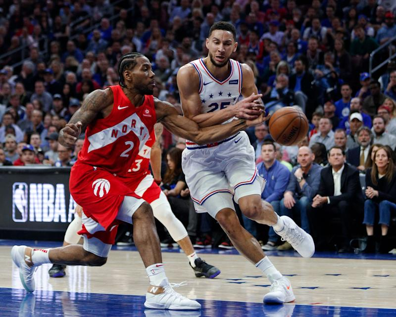 Toronto Raptors' Kawhi Leonard, left, tries to knock the ball away from Philadelphia 76ers' Ben Simmons during the first half of Game 6 of a second-round NBA basketball playoff series Thursday, May 9, 2019, in Philadelphia. (AP Photo/Chris Szagola)