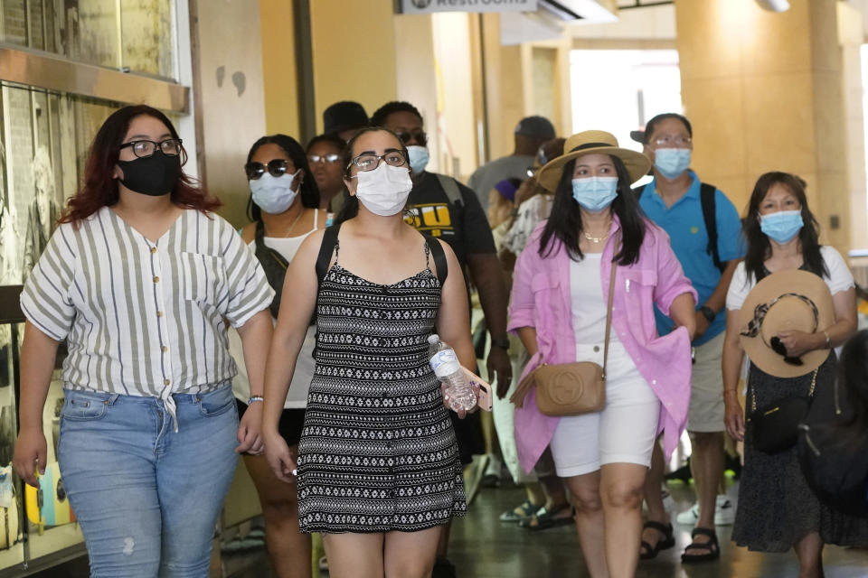 FILE - In this July 1, 2021, file photo visitors wear masks as they walk in a shopping district in the Hollywood section of Los Angeles. A rapid and sustained increase in COVID-19 cases in the nation's largest county requires restoring an indoor mask mandate even when people are vaccinated, Los Angeles County's public health officer said Thursday, July 15, 2021. (AP Photo/Marcio Jose Sanchez, File)