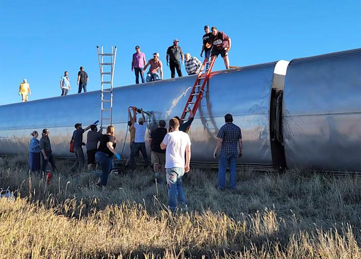 People at the scene help to evacuate passengers from the Amtrak train, which derailed at 4pm on Saturday  (Kimberly Fossen)