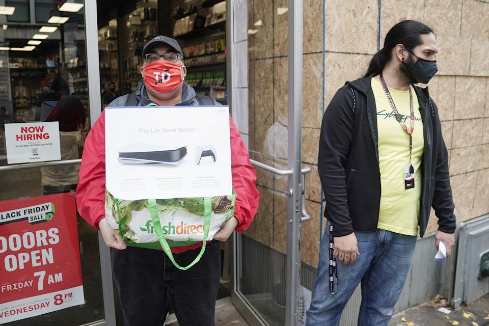 A man poses outside a GameStop store with his purchase of a Sony PS5 gaming console in the Manhattan borough of New York City, New York, U.S., November 12, 2020. REUTERS/Carlo Allegri