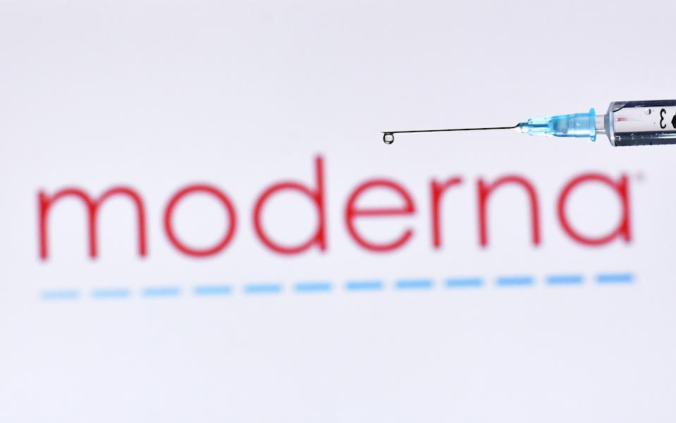 An illustration picture shows a drop from a syringe with the logo of US biotechnology company Moderna on November 17, 2020. (Photo by JUSTIN TALLIS / AFP) (Photo by JUSTIN TALLIS/AFP via Getty Images)