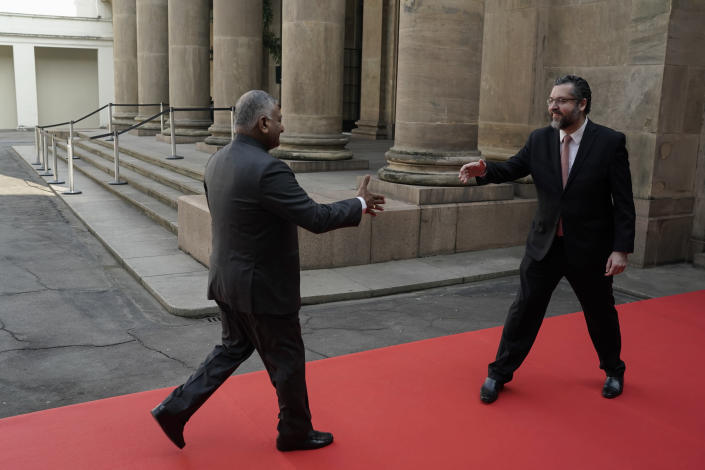Brazil's Foreign Minister Ernesto Araujo receives India's Minister of State for Road Transport Vijay Kumar Singh, left, during a welcome photo session as part of a BRICS representatives meeting in Rio de Janeiro, Brazil, Friday, July 26, 2019. BRICS is a grouping of major emerging economies encompassing Brazil, Russia, India, China and South Africa. The delegations from the BRICS nations begin meeting Friday to pave the way for a summit in November. (AP Photo/Leo Correa)