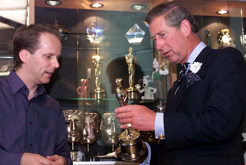 Prince Charles, right, examines an Oscar won by makers of the films starring animated characters Wallace and Gromit with company director Nick Park, in Bristol, England, Monday, July 2, 2001. The Prince laughed and joked with model makers and animators as Park showed him a number of models from the three Wallace and Gromit films and sets from the studio's cinema hit from last year, Chicken Run. (AP Photo/ Paul Grover, Pool)