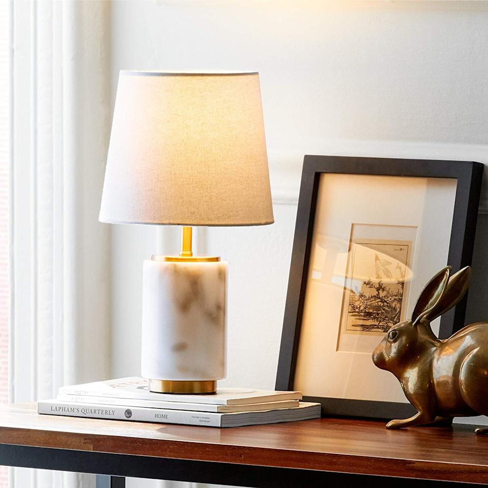 "<p>Add some light and style to any room with this <a href=""https://www.popsugar.com/buy/Rivet-Mid-Century-Modern-Marble-Table-Decor-Lamp-484335?p_name=Rivet%20Mid%20Century%20Modern%20Marble%20Table%20Decor%20Lamp&retailer=amazon.com&pid=484335&price=49&evar1=casa%3Aus&evar9=46598422&evar98=https%3A%2F%2Fwww.popsugar.com%2Fphoto-gallery%2F46598422%2Fimage%2F46598449%2FRivet-Mid-Century-Modern-Marble-Table-Decor-Lamp&list1=shopping%2Chome%20decor%2Chome%20shopping&prop13=api&pdata=1"" rel=""nofollow"" data-shoppable-link=""1"" target=""_blank"" class=""ga-track"" data-ga-category=""Related"" data-ga-label=""https://www.amazon.com/Rivet-Modern-Marble-White-Brass/dp/B075X2YJGK/ref=sr_1_52?keywords=rivet+home+decor&amp;qid=1566858639&amp;s=gateway&amp;sr=8-52"" data-ga-action=""In-Line Links"">Rivet Mid Century Modern Marble Table Decor Lamp</a> ($49, originally $51).</p>"