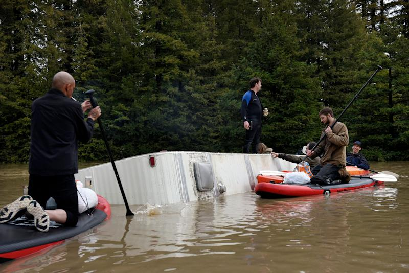 People gather on a partially submerged RV in the flood waters of the Russian River in Forestville, north of San Francisco, Feb. 27, 2019. The rain that swamped the area came from a storm system that also dumped heavy snow in the mountains of California and Nevada and in Washington state, Oregon, Idaho and Montana. (Photo: Michael Short/AP)