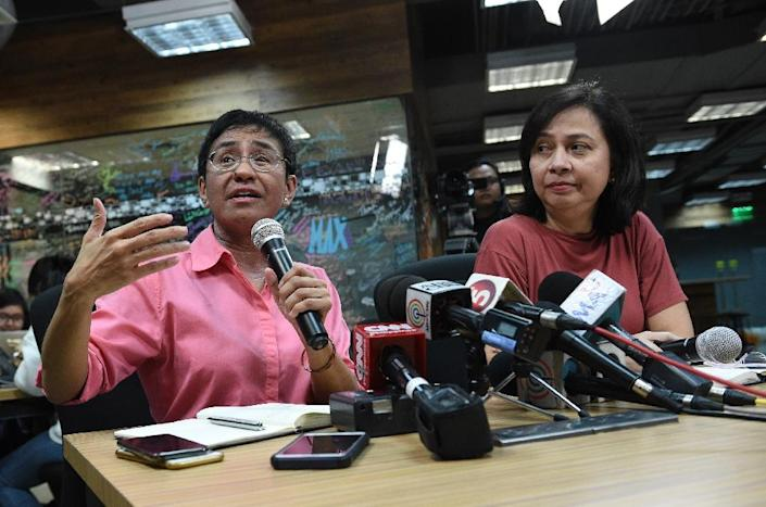 Rappler's acting managing editor Chay Hofilena (R) says the company will file a court appeal against the ruling (AFP Photo/TED ALJIBE)