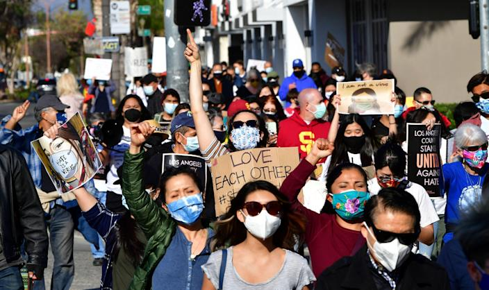 Social activists hold signs as they march from San Gabriel City Hall to Alhambra City Hall in California on March 26, 2021, during an anti-Asian hate rally. The protesters were joined by leaders from the respective cities in the San Gabriel Valley, home to one of the largest Asian American communities in the United States. (Photo by Frederic J. BROWN/AFP via Getty Images)