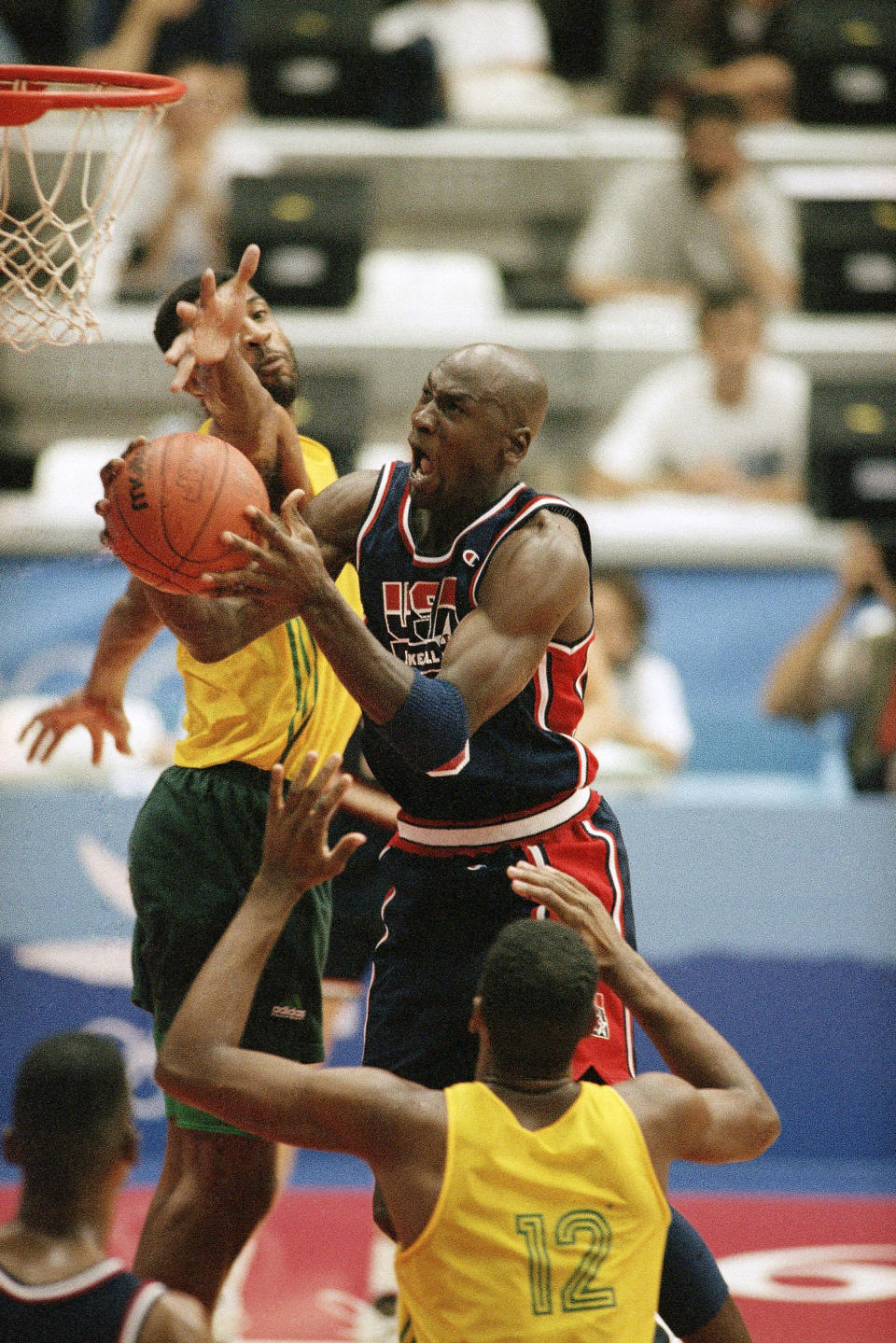 FILE - In this Friday, July 31, 1992, file photo, USA's Michael Jordan takes the ball to the hoop past the outstretched arms of Brazil's Josuel Aristides Santos for two points during first half action of their game at the XXV Summer Olympic Games in Barcelona. USA won the game 127-83. (AP Photo/Stephan Sevoia, FIle)