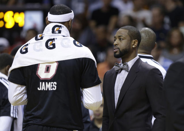 Miami Heat's Dwyane Wade, right, talks with LeBron James during the first half of an NBA basketball game against the Indiana Pacers, Friday, April 11, 2014, in Miami. Wade did not play due to a hamstring injury. (AP Photo/Lynne Sladky)