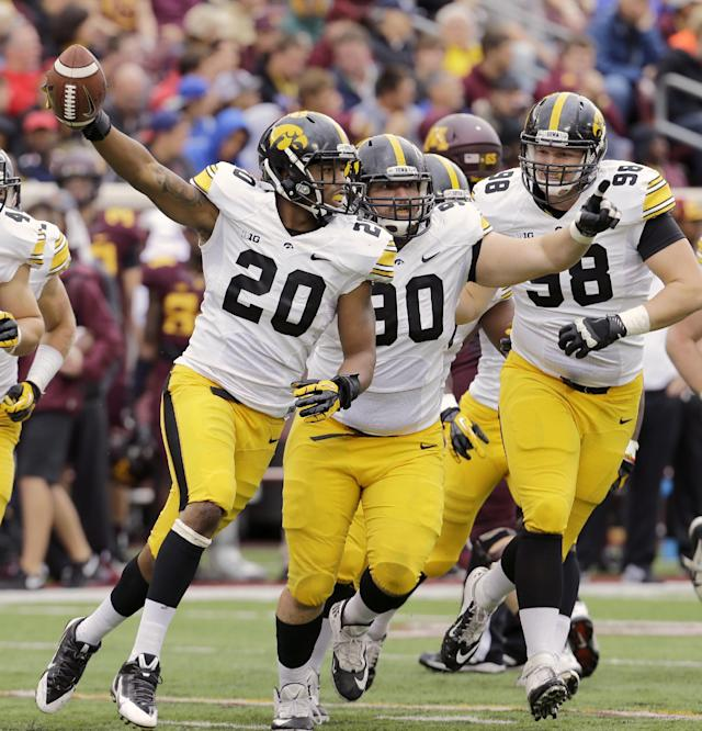 Iowa linebacker Christian Kirksey (20) and defensive lineman Louis Trinca-Pasat, center, and defensive lineman Mike Hardy, right, celebrate after Kirksey intercepted a pass from Minnesota quarterback Philip Nelson (9) during the second quarter of an NCAA college football game on Saturday, Sept. 28, 2013, in Minneapolis. (AP Photo/Ann Heisenfelt)