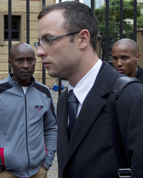Public Oscar Pistorius, center, arrives at the high court for his trial in Pretoria, South Africa, Tuesday, March 11, 2014. Pistorius is charged with murder for the shooting death of his girlfriend, Reeva Steenkamp, on Valentines Day in 2013. (AP Photo/Themba Hadebe)