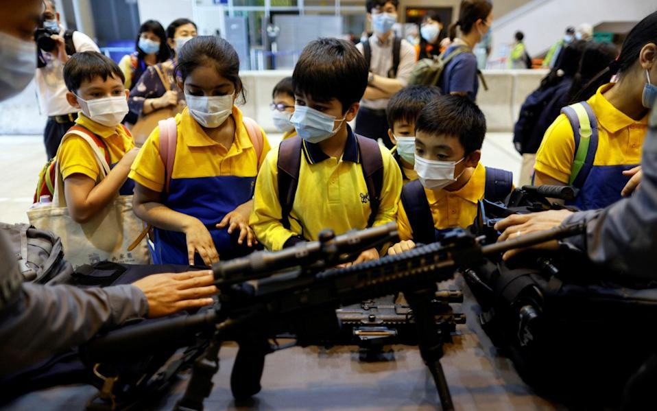 Pupils examine a submachine gun while elsewhere classrooms were decked out in pro-Beijing messages